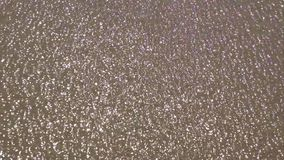 Thin layer of water sparkling in the sand. Stock Photos