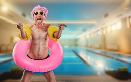 A thin man in a shower cap and a circle around the pool. Royalty Free Stock Photography