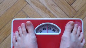 Diet. Excess weight. Thin Man stepping on a scales