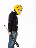 Thin man in yellow helmet and black jacket with bat Stock Image