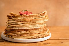 Thin pancakes, blini or crepes on wooden background. With copy space for text. Traditional Russian cuisine, Maslenitsa food royalty free stock photo