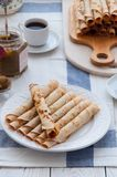 Thin pancakes for breakfast. Maslenitsa. On the table, a dish with pancakes, coffee and jam from feijoa royalty free stock photography