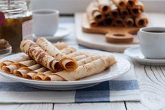 Thin pancakes for breakfast. Maslenitsa. On the table, a dish with pancakes, coffee and jam from feijoa stock image