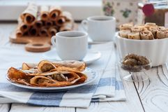 Thin pancakes for breakfast. Maslenitsa. On the table, a dish with pancakes, coffee and jam from feijoa royalty free stock photos