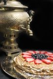 A stack of large pancakes cake from strawberry, blueberry and condensed milk in a metal plate and tea from a old gold samovar on t. Thin pancakes cake from Royalty Free Stock Photo