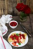 Thin pancakes with cream filling and strawberry sauce on a wooden table. Rustic style stock photo