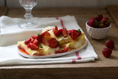 Thin pancakes with cream filling and strawberry sauce on a wooden table. Rustic style. Selective focus royalty free stock photography