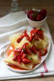 Thin pancakes with cream filling and strawberry sauce on a wooden table. Rustic style. Selective focus stock photos