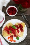 Thin pancakes with cream filling and strawberry sauce on a wooden table. Rustic style. Selective focus stock image