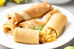 Thin pancakes (crepes) with apple filling, stuffed rolls, Russian traditional food for maslenitsa, French dessert, breakfast with. Tulips on mother's day royalty free stock images