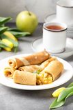 Thin pancakes (crepes) with apple filling, stuffed rolls, Russian traditional food for maslenitsa, French dessert, breakfast with. Tulips on mother\'s day stock photo