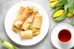 Thin pancakes (crepes) with apple filling, stuffed rolls, Russian traditional food for maslenitsa, French dessert, breakfast with. Tulips on mother\'s day stock images