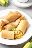 Thin pancakes (crepes) with apple filling, stuffed rolls, Russian traditional food for maslenitsa, French dessert, breakfast with. Tulips on mother\'s day royalty free stock photo