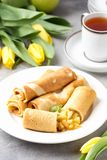 Thin pancakes (crepes) with apple filling, stuffed rolls, Russian traditional food for maslenitsa, French dessert, breakfast with. Tulips on mother\'s day royalty free stock images
