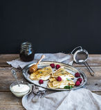 Thin pancakes or crepes with fresh raspberry, cream, mint, on a Stock Photo