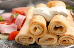 Thin pancakes with garnish on plate. Closeup stock photos