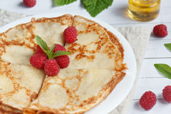 Thin pancakes with honey and raspberries on a white plate.  Royalty Free Stock Photo
