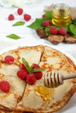 Thin pancakes with honey and raspberries on a white plate.  Royalty Free Stock Photography