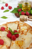 Thin pancakes with honey and raspberries on a white plate.  Stock Photos
