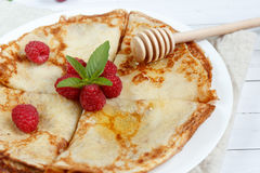Thin pancakes with honey and raspberries on a white plate.  Stock Images