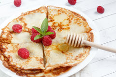 Thin pancakes with honey and raspberries on a white plate.  Stock Photography