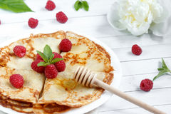 Thin pancakes with honey and raspberries on a white plate.  Royalty Free Stock Image
