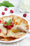 Thin pancakes with honey and raspberries on a white plate.  Royalty Free Stock Images