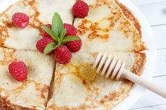 Thin pancakes with honey and raspberries on a white plate.  Stock Photo