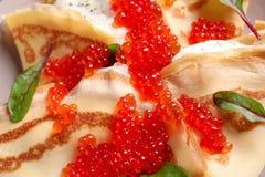 Thin pancakes with red caviar. Closeup Stock Photo