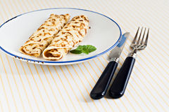 Thin pancakes rolled crepes mint on a plate with knife and fork Royalty Free Stock Photo