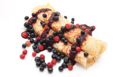 Thin pancakes with sauce. Thin pancakes rolled in a tube watered berry sauce with berries Stock Photo