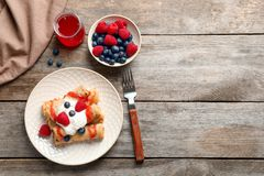Thin pancakes served with syrup, cream. And berries on plate, top view stock photo