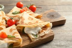 Thin pancakes with sour cream and cherry tomatoes. On wooden board royalty free stock photo