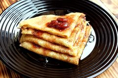 Thin pancakes stacked on a plate and poured with jam royalty free stock image