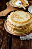 Thin pancakes on a wooden table. Royalty Free Stock Images