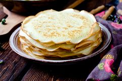 Thin pancakes on a wooden table. Royalty Free Stock Image