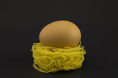 Thin pasta in a form of nest on a dark background. Royalty Free Stock Photo