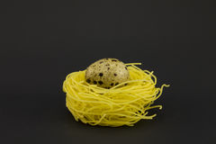 Thin pasta in a form of nest on a dark background. Royalty Free Stock Images