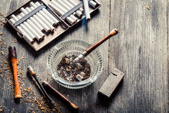 Thin pipe with burning cigarette Stock Photos
