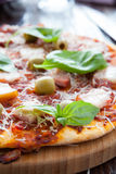 Thin pizza with bacon, olives and basil on board Stock Photos