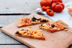 Thin pizza with tomato, grated cheese and herbs Royalty Free Stock Photos