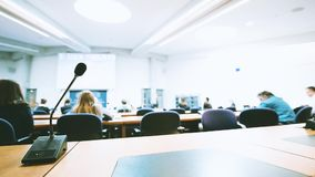 Thin professional microphone in conference room. Focusing to thin professional microphone in lecture conference auditorium room during projection of stock video footage