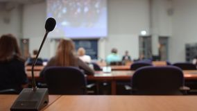 Thin professional microphone in conference room. Thin professional microphone in lecture conference auditorium room during projection of unrecognizable movie a stock footage