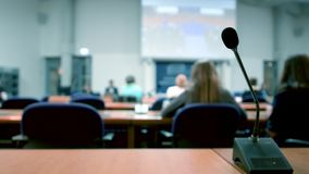 Thin professional microphone in conference room. Thin professional microphone in lecture conference auditorium room during projection of unrecognizable movie a stock video footage