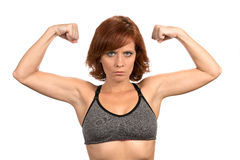 Thin Redhead Woman Flexing Muscles. Thin freckled redheaded woman flexes her bicep muscles while wearing a sports bra Royalty Free Stock Photo