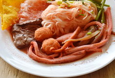 Thin rice noodle with fish line dressing red sauce on dish. Thin rice noodle with fish line dressing red sauce on white dish Stock Photos