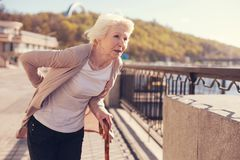 Thin senior woman suffering from herniated disc pain. Hard to walk. Thin white-haired senior woman leaning on a cane and touching her sore lower back suffering Stock Photos