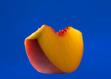 Thin slice of peach isolated on blue. Thin slice of peach on blue background Royalty Free Stock Photo