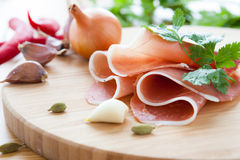 Thin slices of ham on the board Stock Photography