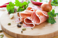 Thin slices of ham with herbs and spices Stock Photography